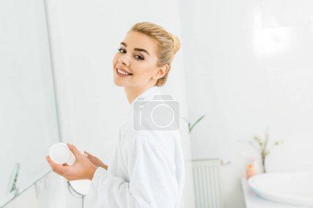 Photo pour Femme souriante en peignoir blanc tenant crème cosmétique et en regardant la caméra dans la salle de bain - image libre de droit