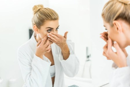 selective focus of attractive and blonde woman in white bathrobe attaching contact lens in bathroom