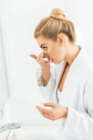 Photo pour Femme belle et blonde en peignoir blanc y attacher des lentilles de contact dans la salle de bain - image libre de droit