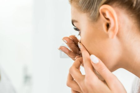 selective focus of attractive and blonde woman in white bathrobe attaching contact lens