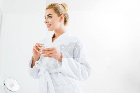 Photo pour Femme belle et souriante en peignoir tenant parfum dans la salle de bain - image libre de droit