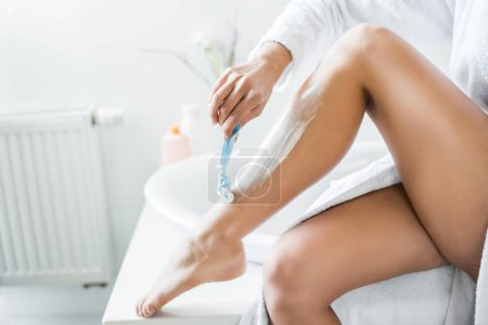 Photo for Partial view of young adult woman shaving leg with razor in bathroom - Royalty Free Image