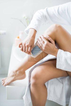 Photo pour Vue partielle de la jeune femme adulte épilation jambe avec bande Epilation dans salle de bain - image libre de droit