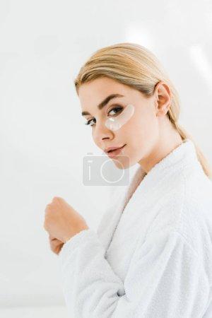 Photo pour Femme belle et blonde en peignoir blanc avec pansements oculaires sur le visage en regardant la caméra dans la salle de bain - image libre de droit