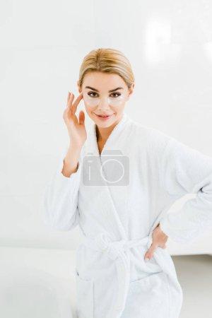Photo pour Belle femme blonde en peignoir blanc avec des patchs sur le visage en regardant la caméra dans la salle de bain - image libre de droit