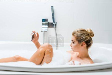 Photo pour Vue latérale de la femme attrayante et blonde prenant un bain avec de la mousse et prenant selfie dans la salle de bain - image libre de droit