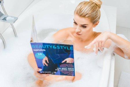 Photo pour Foyer sélectif de femme attrayante et blonde prenant un bain avec de la mousse et pointant du doigt le magazine de beauté et de style - image libre de droit