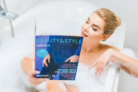 Photo for Selective focus of attractive and blonde woman taking bath with foam and reading beauty and style magazine in bathroom - Royalty Free Image