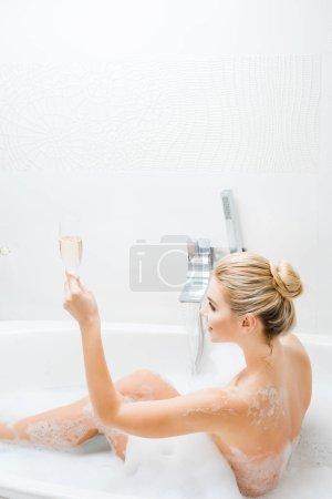 Photo pour Belle et souriante femme prenant bain et tenant verre de champagne dans la salle de bain - image libre de droit