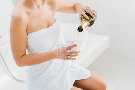 Photo for Cropped view of woman in towel holding champagne glass and bottle in bathroom - Royalty Free Image