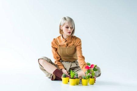 Photo pour Belle fille blonde élégante assise avec des pots de fleurs sur blanc - image libre de droit