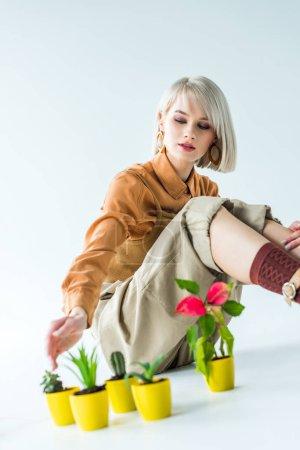 Photo pour Foyer sélectif de belle fille élégante assis avec des greffes de fleurs sur blanc - image libre de droit