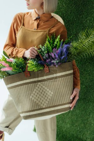 cropped view of stylish young woman holding bag with fern and flowers on white with green grass