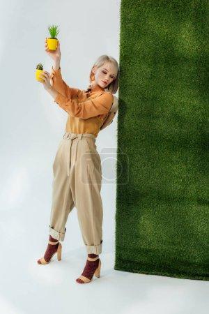 schöne stilvolle blonde Mädchen mit Blumentöpfen auf grau mit grünem Gras