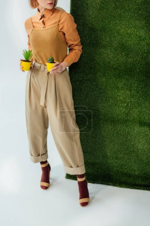 cropped view of stylish girl holding flower pots on grey with green grass