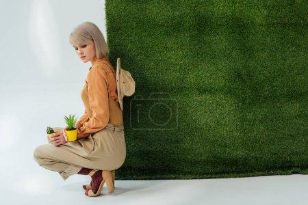Photo pour Belle fille élégante assise et tenant des pots de fleurs sur gris avec herbe verte - image libre de droit