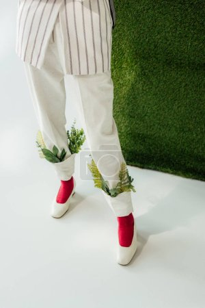 Photo for Low section of woman in white pants with green leaves and stylish shoes - Royalty Free Image