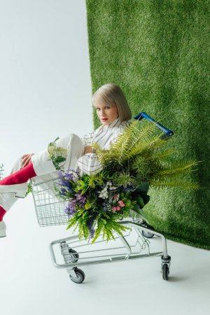 beautiful stylish girl looking at camera while sitting in shopping cart with fern and flowers on white with green grass