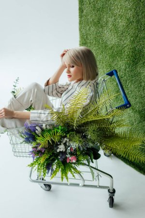 beautiful stylish girl sitting in shopping cart with fern and flowers on white with green grass