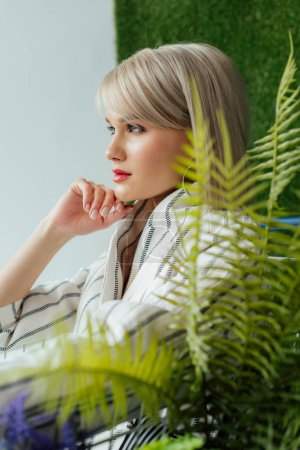 Photo for Side view of beautiful stylish blonde girl posing near fern leaves - Royalty Free Image