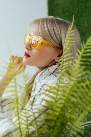 Photo for Beautiful stylish girl in sunglasses posing near fern leaves - Royalty Free Image