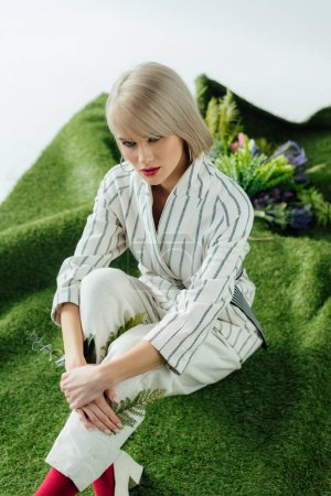 Photo for Beautiful stylish blonde girl posing on artificial grass with fern leaves - Royalty Free Image