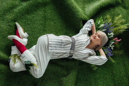 Photo for High angle view of beautiful stylish girl smiling while lying on artificial grass with flowers - Royalty Free Image