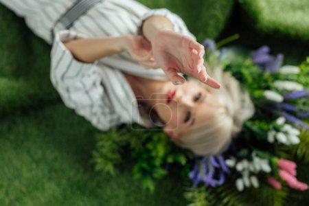 Photo pour Fille élégante avec la main tendue, parsemée de plantes sur gazon artificiel - image libre de droit