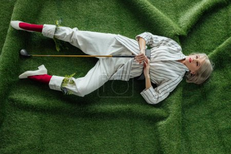 Photo for High angle view of beautiful stylish girl lying with golf club on artificial grass - Royalty Free Image