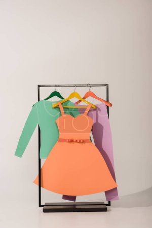Photo for Rack with colorful paper clothes on white - Royalty Free Image