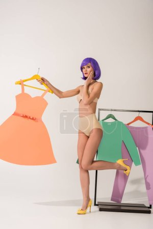 Photo for Beautiful surprised girl with purple hair holding paper dress and posing near rack with colorful clothes on white - Royalty Free Image