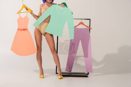 Photo for Partial view of girl in underwear posing with colorful paper clothes on white - Royalty Free Image