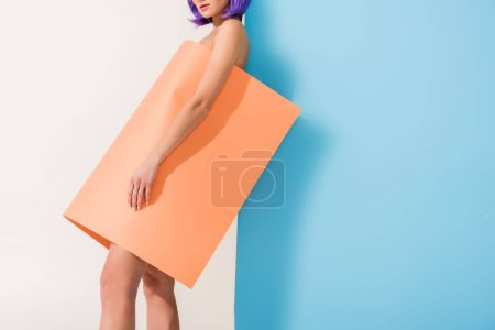 Photo for Cropped view of girl covered in coral paper sheet posing on blue and white with copy space - Royalty Free Image