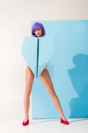 beautiful young woman with purple hair looking at camera while posing with paper plane on blue and white