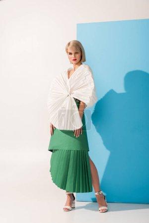 Photo pour Belle fille à la mode dans les vêtements de papier posant sur bleu et blanc - image libre de droit