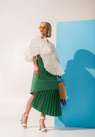 Photo pour Belle fille élégante lunettes de soleil et vêtements de papier posant sur bleu et blanc - image libre de droit