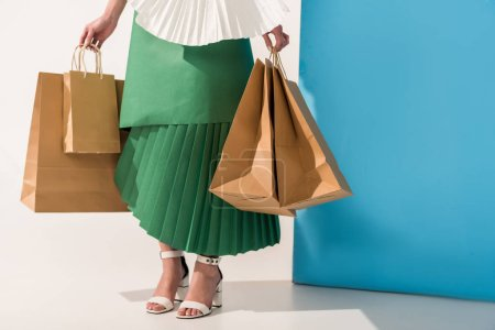 Photo for Cropped view of stylish girl in paper clothes with shopping bags on blue and white - Royalty Free Image