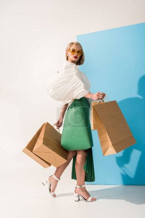 beautiful stylish girl in sunglasses and paper clothes posing with shopping bags on blue and white