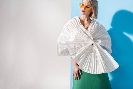 Foto de Hermosa chica con estilo en gafas de sol y ropa de papel posando en azul y gris con espacio de copia - Imagen libre de derechos