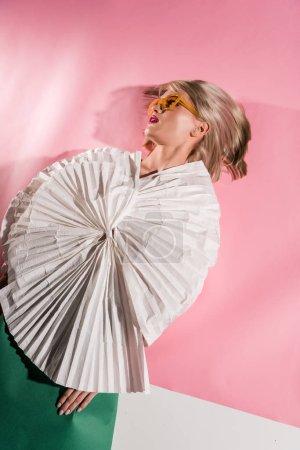 Foto de Hermosa chica con estilo en gafas de sol y ropa de papel en rosa y blanco - Imagen libre de derechos