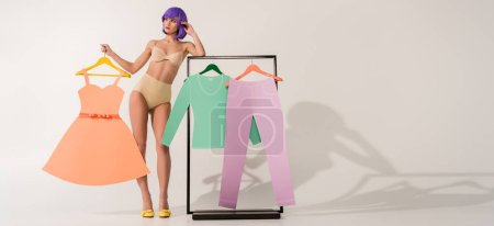 Photo for Panoramic shot of beautiful girl with purple hair posing near rack with paper clothes on white with copy space - Royalty Free Image