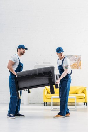 Photo for Two movers in uniform transporting furniture in apartment with copy space - Royalty Free Image