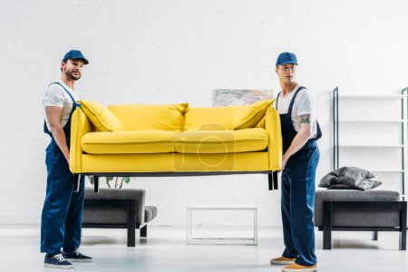 Photo for Two movers in uniform transporting couch in apartment - Royalty Free Image