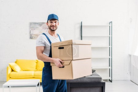 Photo for Handsome mover in uniform looking at camera while carrying cardboard boxes in apartment with copy space - Royalty Free Image