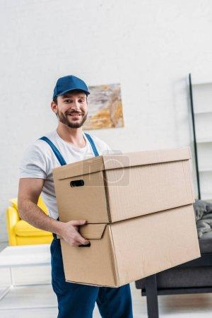 Foto de Guapo mover en uniforme mirando a la cámara mientras lleva cajas de cartón en el apartamento - Imagen libre de derechos