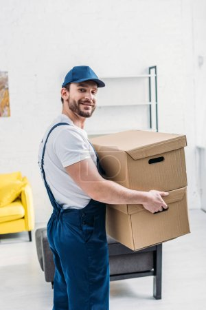 Photo pour Beau déménageur en uniforme regardant la caméra tout en portant des boîtes en carton dans l'appartement - image libre de droit