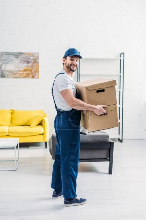 Photo for Mover in uniform looking at camera while carrying cardboard boxes in apartment - Royalty Free Image