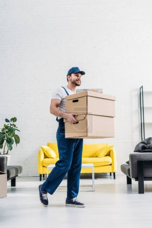Photo for Mover in uniform carrying cardboard boxes in modern apartment - Royalty Free Image
