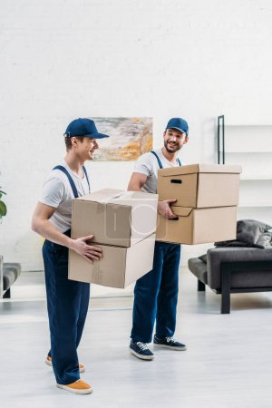 Photo for Two smiling movers in uniform carrying cardboard boxes in apartment - Royalty Free Image