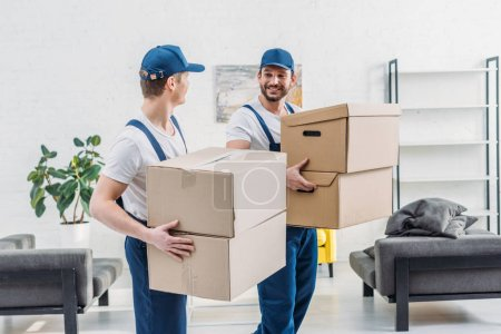 Photo for Two movers in uniform looking at each other while carrying cardboard boxes in apartment - Royalty Free Image
